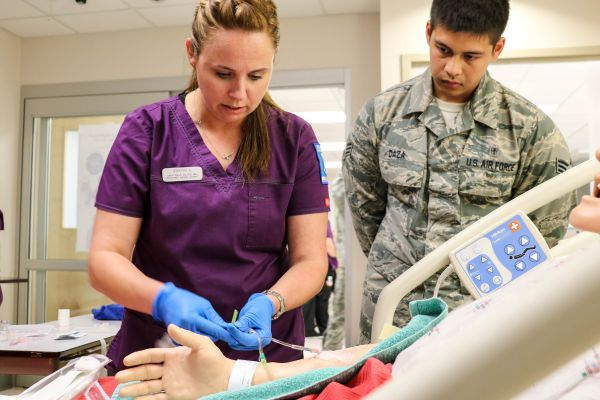 A Great Falls College MSU nursing student demonstrates how to start an IV, while an airman from Malmstrom Air Force Base looks on. GFC MSU and Malmstrom have partnered to offer training courses to help some of the medical staff on base refresh their skills